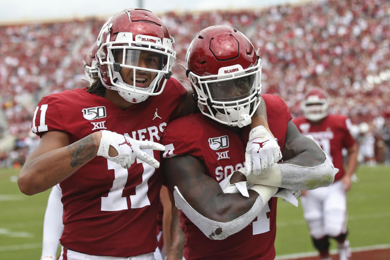 Oklahoma wide receiver Jadon Haselwood (11) and running back Trey Sermon (4) celebrate Sermon's touchdown in the third quarter of an NCAA college football game against Texas Tech in Norman, Okla., Saturday, Sept. 28, 2019. (AP Photo/Sue Ogrocki)