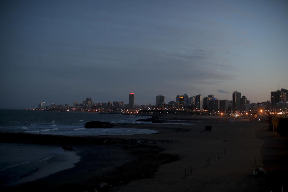 The sun sets during the COVID-19 pandemic in Mar del Plata, Argentina, Saturday, Oct. 10, 2020. The resort's new reality is starkly visible: Its beaches and businesses are deserted at a time when Argentines normally would be booking lodging and renting beach gear for the fast-approaching Southern Hemisphere summer. (AP Photo/Natacha Pisarenko)