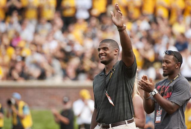 Former Missouri player Michael Sam, left, waves to fans has he and former teammate E.J. Gaines, right, are introduced during the first quarter of the South Dakota State-Missouri NCAA college football game Saturday, Aug. 30, 2014, in Columbia, Mo. The St. Louis Rams cut Michael Sam, the first openly gay player drafted by an NFL team. Coach Jeff Fisher repeated over and over that it was purely a football decision. (AP Photo/L.G. Patterson)