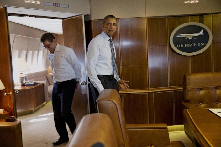 President Barack Obama enters a conference room past White House press secretary Jay Carney to sign an executive order streamlining the export/import process for American business, Wednesday, Feb. 19, 2014, during a flight aboard Air Force One en route to Toluca, Mexico. In Mexico, the president is expected to participate in the seventh trilateral North American Leaders Summit Meeting. (AP Photo/Jacquelyn Martin)