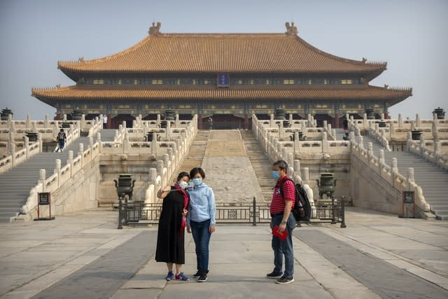 Visitors wearing face masks to protect against the new coronavirus pose for a selfie in the Forbidden City in Beijing (AP)