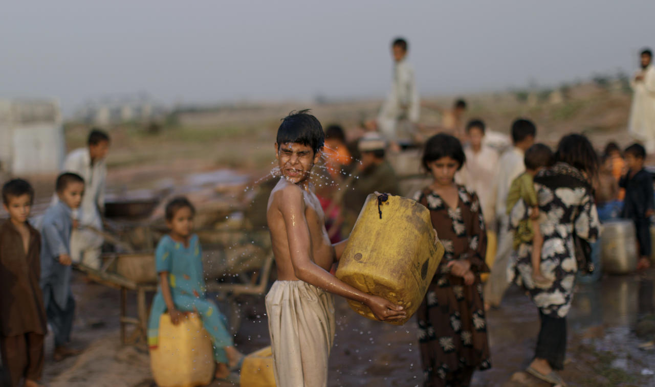 An Afghan refugee boy washes his face while waiting with others to collect water at a point in a slum area on the outskirts of Islamabad, Pakistan, Monday, June 20, 2011. World Refugee Day is observed on Monday. (AP Photo/Muhammed Muheisen)