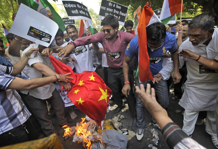 FILE- In this May 1, 2013 file photo, Indian protesters burn a Chinese flag and shout slogans against the alleged incursion by Chinese troops into Indian territory, during a protest in New Delhi, India. While the recent troop standoff in a remote Himalayan desert spotlights a long-running border dispute between China and India, the two emerging giants are engaged in a rivalry for global influence that spreads much farther afield. (AP Photo /Manish Swarup, File)