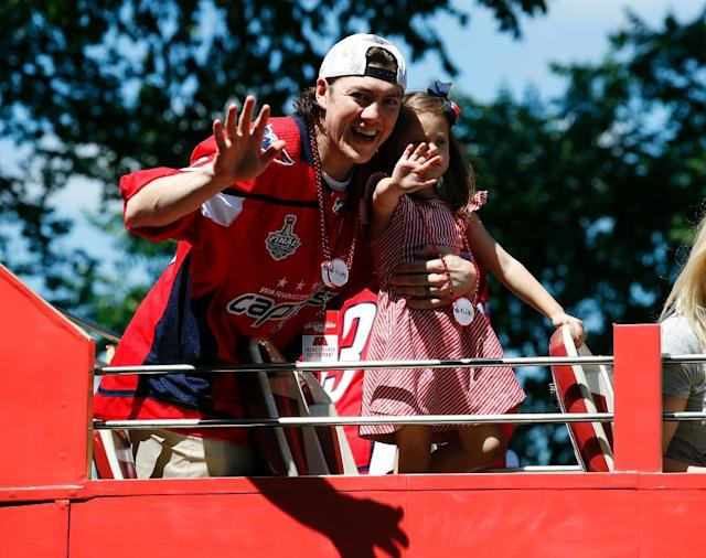 Washington Capitals winger T.J. Oshie waves to the crowd while holding his daughter Lyla during the team's Stanley Cup parade (AFP Photo/Alex Brandon)