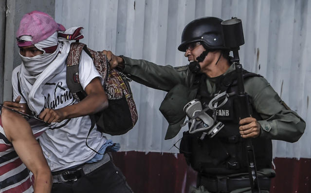 <p>An anti-government activist is grabbed by a member of the National Guard during clashes in Caracas on July 27, 2017 on the second day of a 48-hour general strike called by the opposition. (Photo: Juan Barreto/AFP/Getty Images) </p>