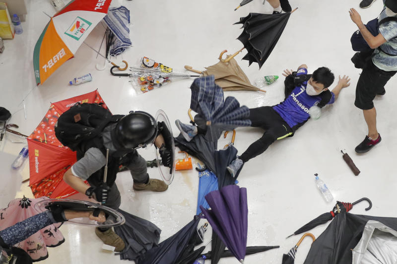 In this Sunday, July 14, 2019, photo, policemen scuffle with protesters inside a shopping mall in Sha Tin District in Hong Kong. Police in Hong Kong have fought with protesters as they broke up a demonstration by thousands of people demanding the resignation of the Chinese territory's chief executive and an investigation into complaints of police violence. (AP Photo/Kin Cheung)