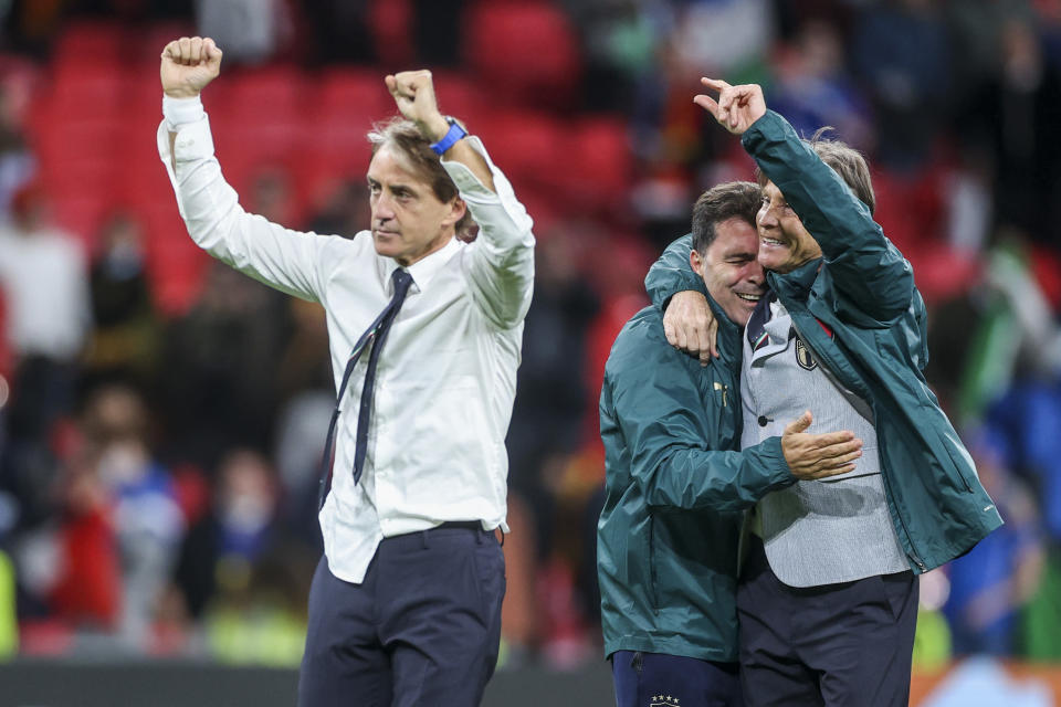 Italy's manager Roberto Mancini, left, celebrates after winning the Euro 2020 soccer championship semifinal match against Spain at Wembley stadium in London, England, Tuesday, July 6, 2021. (Carl Recine/Pool Photo via AP)