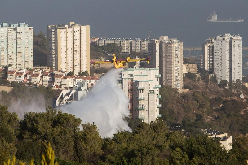 A firefighting plane helps extinguish a fire in the northern Israeli city of Haifa following a wildfire, on November 25, 2016 (AFP Photo/Menahem Kahana)