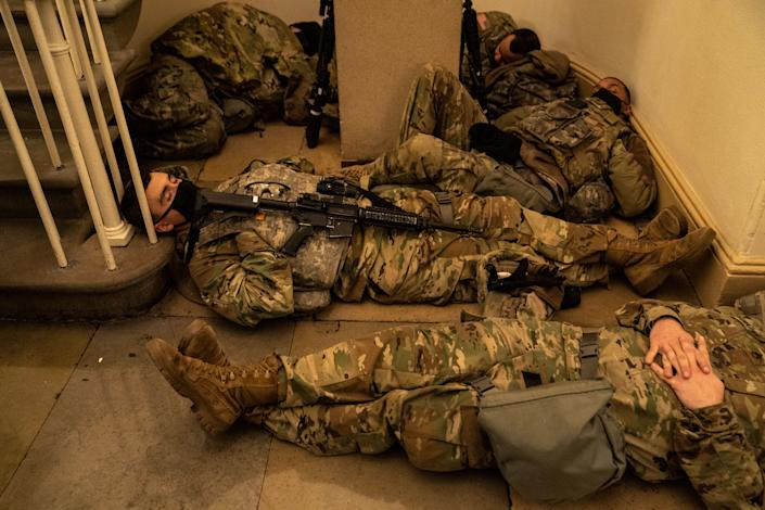 WASHINGTON, DC - JANUARY 13: Members of the National Guard sleep in the halls of Capitol Hill as the House of Representativs convene to impeach President Donald Trump, nearly a week after a pro-Trump insurrectionist mob breached the security of the nations capitol while Congress voted to certify the 2020 Election Results on Wednesday, Jan. 13, 2021 in Washington, DC. (Kent Nishimura / Los Angeles Times via Getty Images)