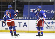 New York Rangers' K'Andre Miller (79) congratulates teammate Brendan Smith (42) after Smith scored a goal in the first period against the Philadelphia Flyers during an NHL hockey game Thursday, April 22, 2021, in New York. (Elsa/Pool Photo via AP)