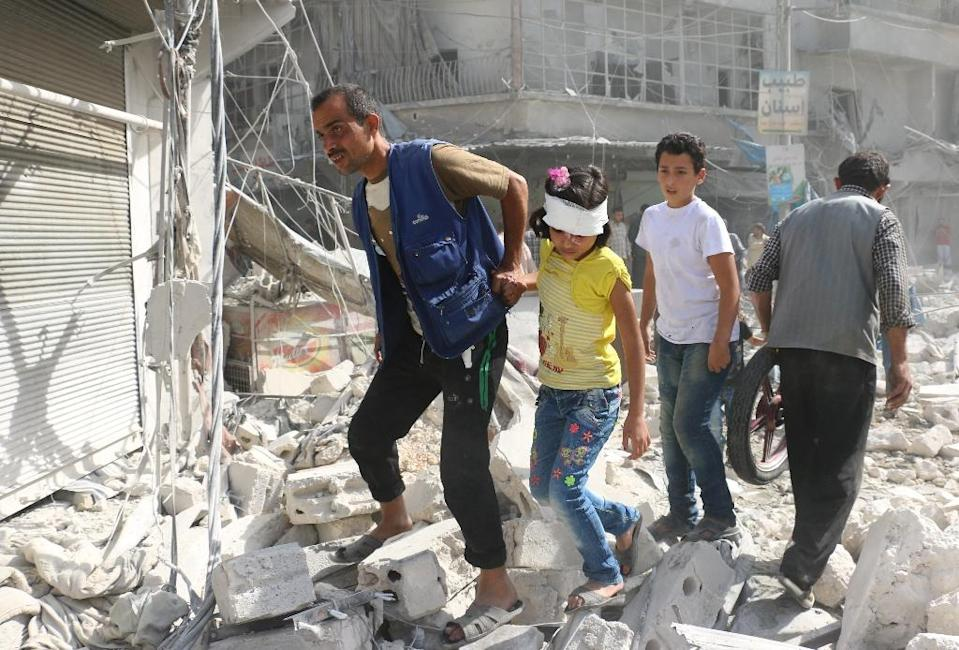 Syrians walk over rubble following air strikes on the rebel-held Fardous neighbourhood of Aleppo (AFP Photo/Ameer Alhalbi)
