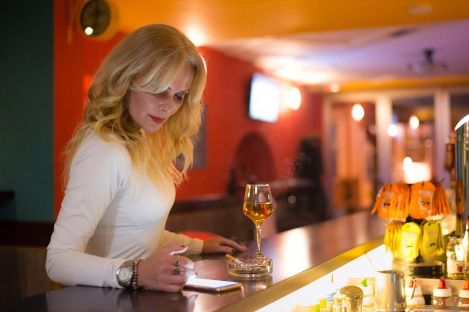 older cougar woman drinking alone at bar checking her phone for message