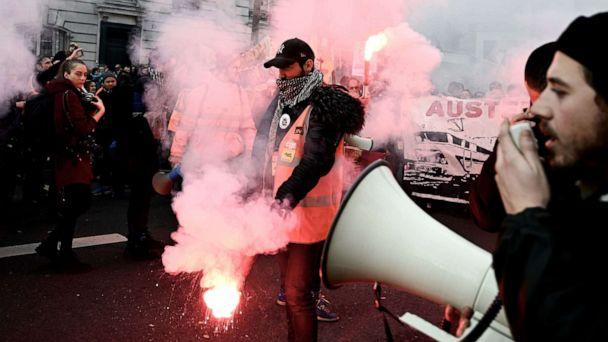 PHOTO: A man with a vest of the French state railway company SNCF burns flares next to a man speaking in a loud speaker during a demonstration in Paris, Dec. 17, 2019. (Philippe Lopez/AFP via Getty Images)