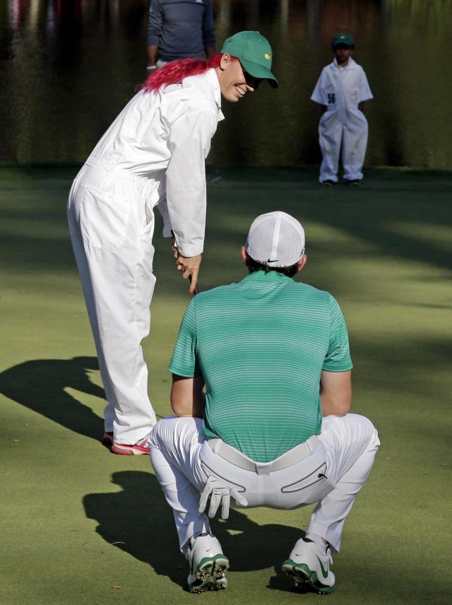 Tennis player Caroline Wozniacki gets advice from her fiancee Rory McIlroy, of Northern Ireland, before putting on the ninth hole during the par three competition at the Masters golf tournament Wednesday, April 9, 2014, in Augusta, Ga. (AP Photo/Chris Carlson)