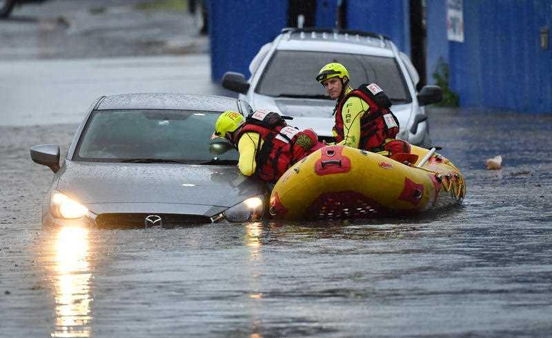 A Swift Water Rescue team from the Queensland Fire and Emergency Services are seen searching flooded cars on Longlands Street at Woolloongabba in Brisbane.