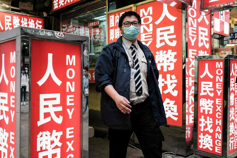 A security worker walks past a money exchange outlet in Hong Kong. Photo: AFP