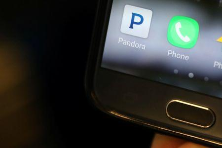 A person holds a smart phone with the Pandora app showing in New York