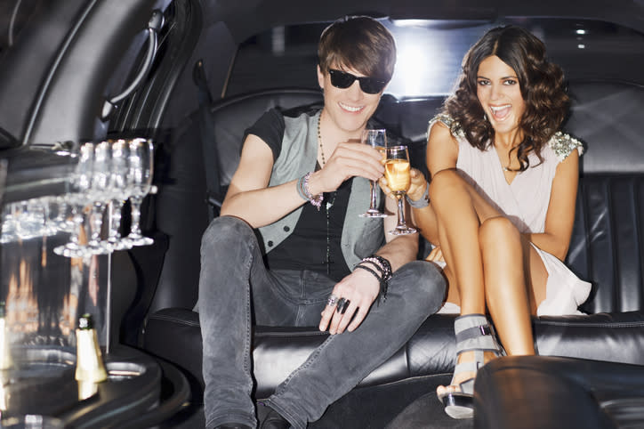 Couple toasting each other in limousine.