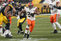 Cleveland Browns running back Nick Chubb (24) runs through a hole during the first half of an NFL wild-card playoff football game against the Pittsburgh Steelers, Sunday, Jan. 10, 2021, in Pittsburgh. (AP Photo/Keith Srakocic)