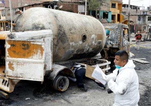 Forensic police inspect the wreckage of a gas tanker that exploded in Lima