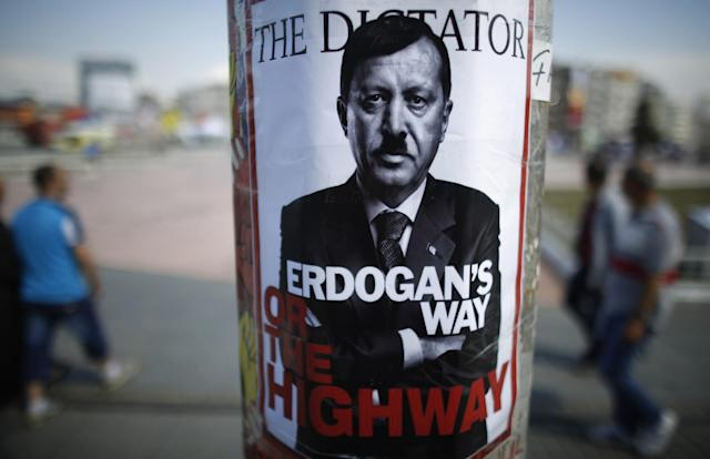 <p>People walk past a poster depicting Turkish Prime Minister Tayyip Erdogan that has been pasted by demonstrators at Taksim Square in Istanbul June 5, 2013. (Stoyan Nenov/Reuters) </p>