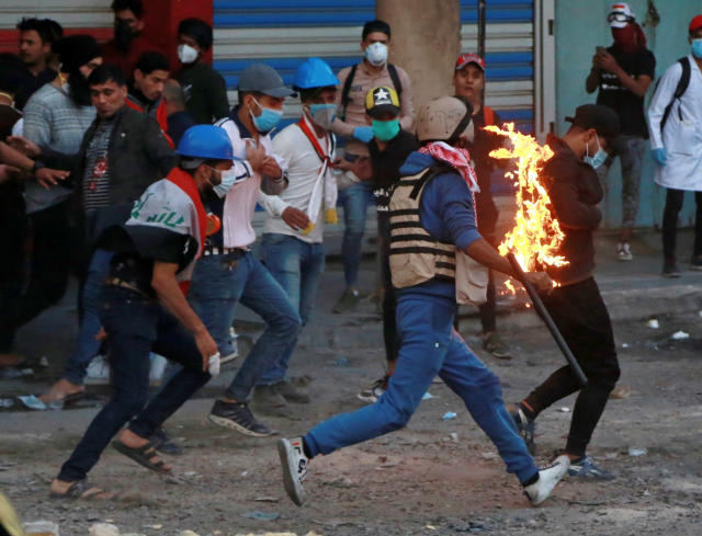 Demonstrators try to extinguish a protester who has caught fire, during clashes between Iraqi security forces and anti-Government protesters, in Baghdad, Iraq, Nov. 21, 2019. (Photo: Khalid Mohammed/AP)