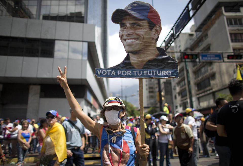 A woman holds up a banner with the image of Venezuelan opposition leader Henrique Capriles as people gather for a demonstration against President Nicolas Maduro in Caracas, Venezuela, Saturday, April 8, 2017. Capriles was banned from running for office for 15 years. Opponents of President Nicolas Maduro are preparing to flood the streets of Caracas on Saturday as part of a week-long protest movement that shows little sign of losing steam. (AP Photo/Ariana Cubillos)