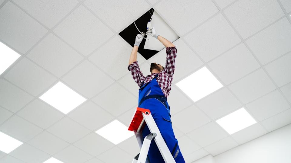 Full Length Portrait Of Electrician On Stepladder Installs Lighting To The Ceiling In Office.