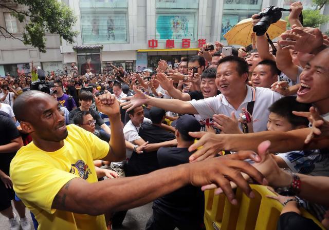 """<p> FILE - In this Aug. 16, 2012 file photo, Los Angeles Lakers' Kobe Bryant, left, shakes hands with Chinese fans during a """"meet the fans"""" event in Wuhan in central China's Hubei province. He has not uttered one word yet, Bryant's mere presence on a Twitter-like Chinese-language site has stirred plenty of excitement. Sina Weibo has verified that the NBA superstar has set up an individual account on its hugely popular microblogging site. Bryant's followers numbered more than 100,000 within hours on Thursday, Feb. 14, 2013, although no comments from Bryant had appeared. (AP Photo) CHINA OUT </p>"""