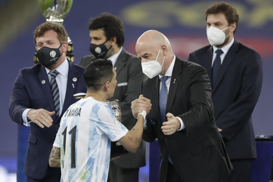 FIFA President Gianni Infantino, right, greets Argentina's Angel Di Maria at the award ceremony after his team won 1-0 against Brazil in the Copa America final soccer match at the Maracana stadium in Rio de Janeiro, Brazil, Saturday, July 10, 2021. (AP Photo/Andre Penner)