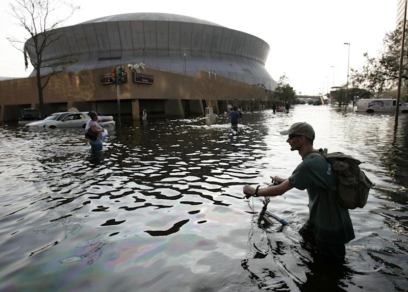FILE - This Aug, 31, 2005 file photo shows a man pushing his bicycle through flood waters near the Superdome in  New Orleans after Hurricane Katrina left much of the city under water. Hurricane responses by politicians mean avoiding disaster _ their own. Katrina's legacy looms large as Isaac heads toward New Orleans and politicians from local Gulf Coast parishes to the White House and the Republican convention host city of Tampa, Fla., are calibrating their actions and their words, mindful of the sensitivities of how the public will perceive them.   (AP Photo/Eric Gay, File)