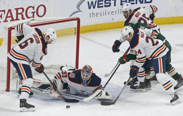 Edmonton Oilers' Adam Larsson, left, of Sweden, and Brad Malone, right, assist goalie Cam Talbot as Minnesota Wild's Zach Parise, in middle at right, can't reach the rebound during the first period of an NHL hockey game Thursday, Feb. 7, 2019 in St. Paul, Minn. (AP Photo/Jim Mone)
