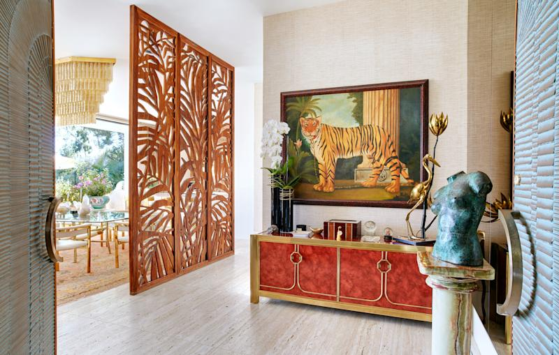 In the entryway, a vintage oil painting of a tiger hangs above a vintage faux-bamboo-and-lacquer credenza by Mastercraft. The palm-leaf walnut screen is a custom design.