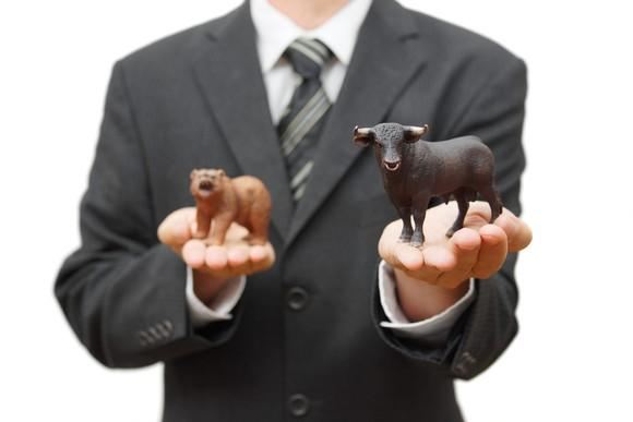 A person in a suit is holding a toy bull in one hand and a toy bear in the other.