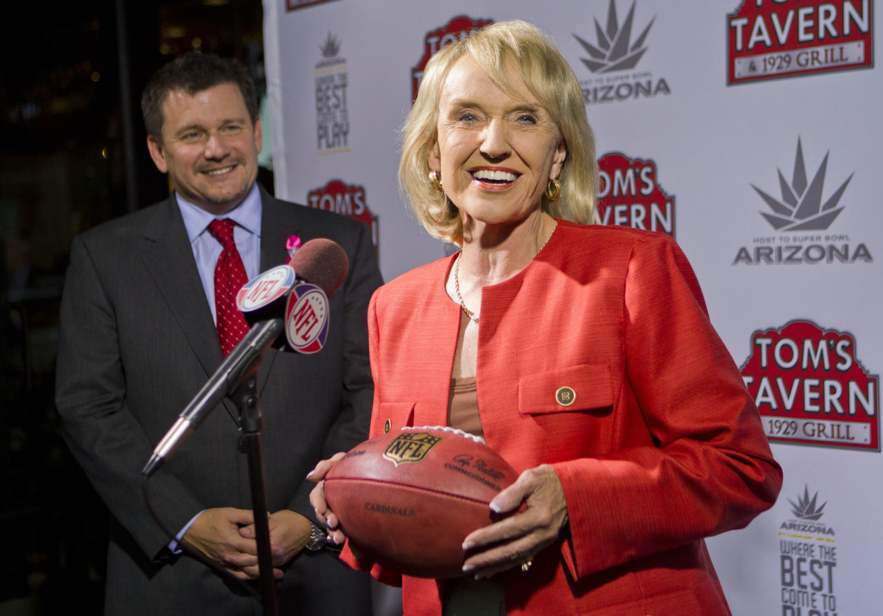 Arizona Cardinals president Michael Bidwill, left, and Arizona Gov. Jan Brewer smile Tuesday, Oct. 11, 2011, in Phoenix, after NFL owners awarded the 2015 Super Bowl football game to the Phoenix area. (AP Photo/The Arizona Republic, Michael Chow) MARICOPA COUNTY OUT NO SALES