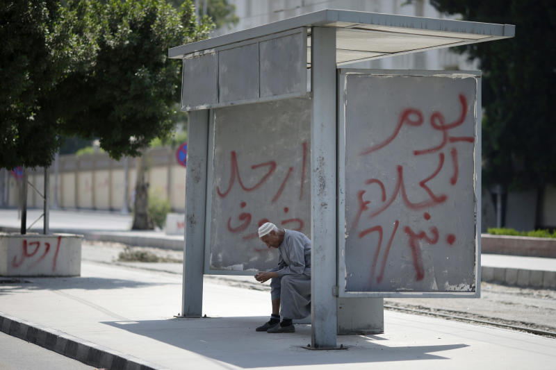 "An Egyptian man waits at train stop in front of the presidential palace, days ahead of planned protests against the country's Islamist President Mohammed Morsi in Cairo, Egypt, Friday, June 28, 2013. Arabic reads, ""leave, left, evacuation day.""(AP Photo/Hassan Ammar)"