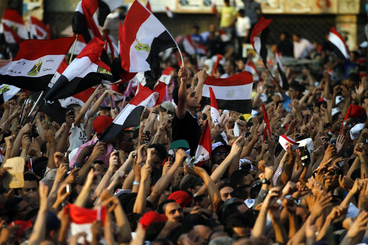 Egyptian protesters react as they listen to the speech of Egypt's President-elect Mohammed Morsi, in Tahrir Square in Cairo, Egypt, Friday, June 29, 2012. In front of tens of thousands of cheering supporters, Egypt's first Islamist and civilian president-elect vowed Saturday that nobody can take away his authority and symbolically read an oath of office in Cairo's Tahrir Square on the eve of his official inauguration. (AP Photo/Khalil Hamra)