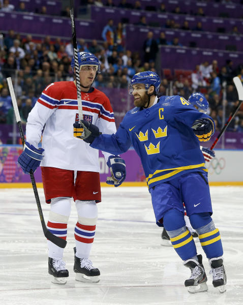 Sweden forward Henrik Zetterberg, right, reacts in front of Czech Republic defenseman Tomas Kaberle after Sweden scored a goal in the second period of a men's ice hockey game at the 2014 Winter Olympics, Wednesday, Feb. 12, 2014, in Sochi, Russia. (AP Photo/Mark Humphrey)