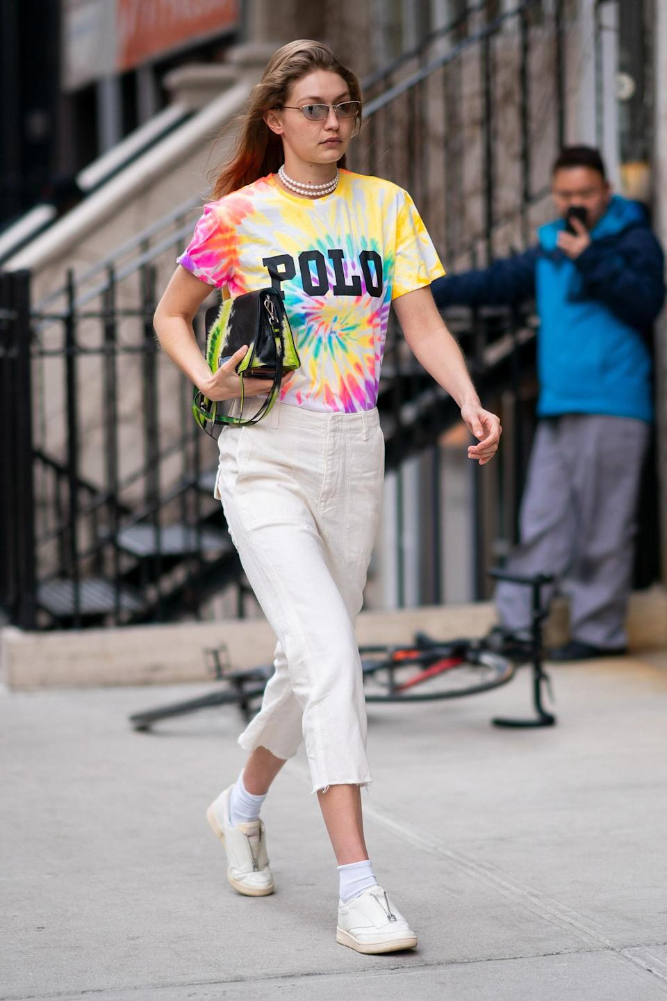 Tie-dye take two! Gigi looks like the summer camp counselor of our dreams, pairing a rainbow-hued t-shirt with cropped khakis and a green and black tie-dyed purse. The only thing missing is a stack of friendship bracelets!
