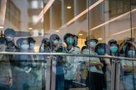 Bystanders watch protesters on a street below a shop during a rally against a new national security law in Hong Kong on July 1, 2020
