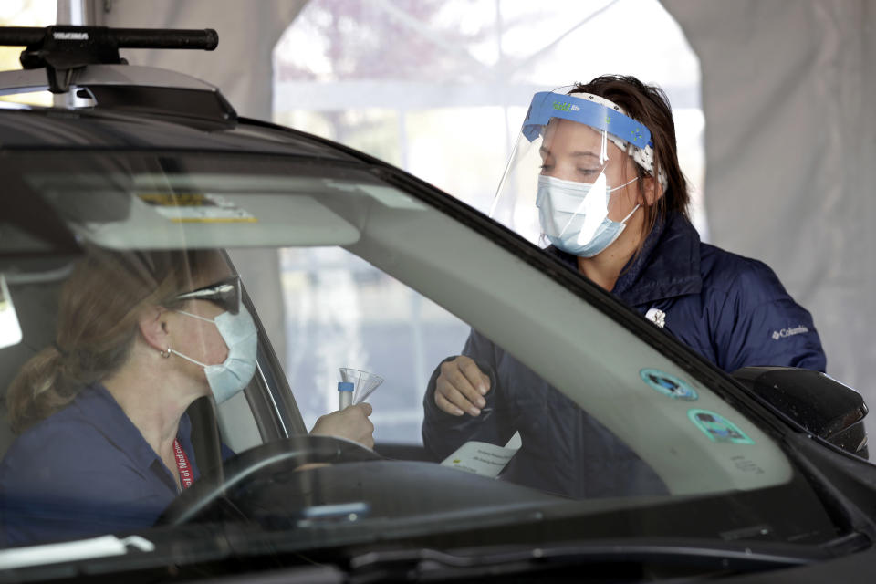 Nursing assistant Monica Brodsky, right, hands over a funnel and vial for a saliva test, that tests for COVID-19, to Janet Legare, of Middleton, Wis., during drive-thru testing in the parking lot at UW Health Administrative Office Building in Middleton, Monday, Oct. 5, 2020. A surge of coronavirus cases in Wisconsin and the Dakotas is forcing a scramble for hospital beds and raising political tensions, as the Upper Midwest and Plains emerge as one of the nation's most troubling hotspots. (Amber Arnold/Wisconsin State Journal via AP)