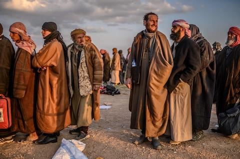<span>Men suspected of being Isil fighters wait to be searched by members of the Kurdish-led Syrian Democratic Forces (SDF) after leaving the group's last holdout of Baghouz</span> <span>Credit: AFP </span>