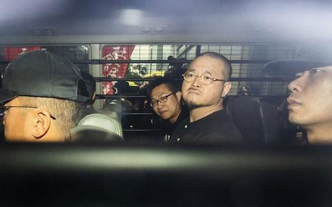 Raphael Wong, center left, and Shiu Ka-chun, center right, sit in a van as they leave court following their sentencing on Wednesday - Credit: Justin Chin/Bloomberg