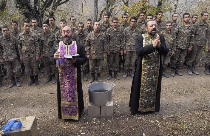 Priests Aristakes Hovhannisyan, left, and Sebeos Galachyan conduct a baptism ceremony for ethnic Armenian soldiers in a military camp near the front line during a military conflict in separatist region of Nagorno-Karabakh, Monday, Nov. 2, 2020. Fighting over the separatist territory of Nagorno-Karabakh entered sixth week on Sunday, with Armenian and Azerbaijani forces blaming each other for new attacks. (AP Photo)