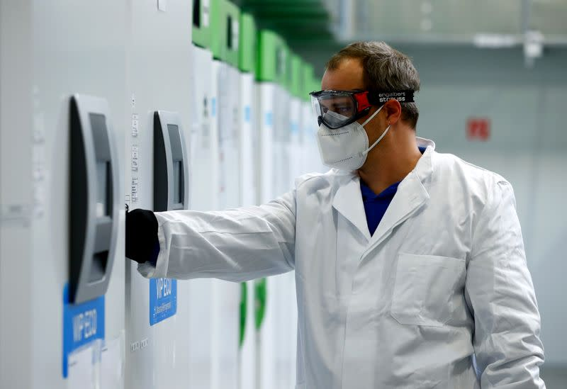 FILE PHOTO: An employee opens an ultra-cold refrigerator filled with vaccines against the coronavirus disease (COVID-19) at a secret storage facility in the Rhein-Main area