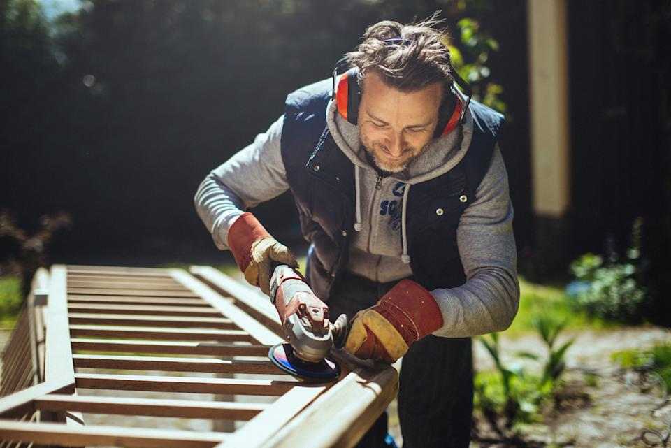 Smiling man grinding an old handrail in the garden.