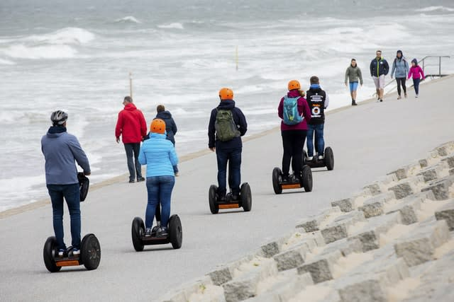 People travel on Segways along the Norderney coast in Germany