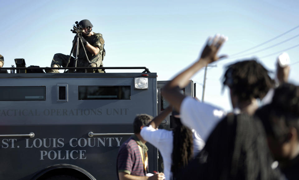 FILE - In this Wednesday, Aug. 13, 2014 file photo, a member of the St. Louis County Police Department points his weapon in the direction of a group of protesters in Ferguson, Mo. On Saturday, Aug. 9, 2014, a white police officer fatally shot Michael Brown, a Black teenager, in the St. Louis suburb. (AP Photo/Jeff Roberson, File)