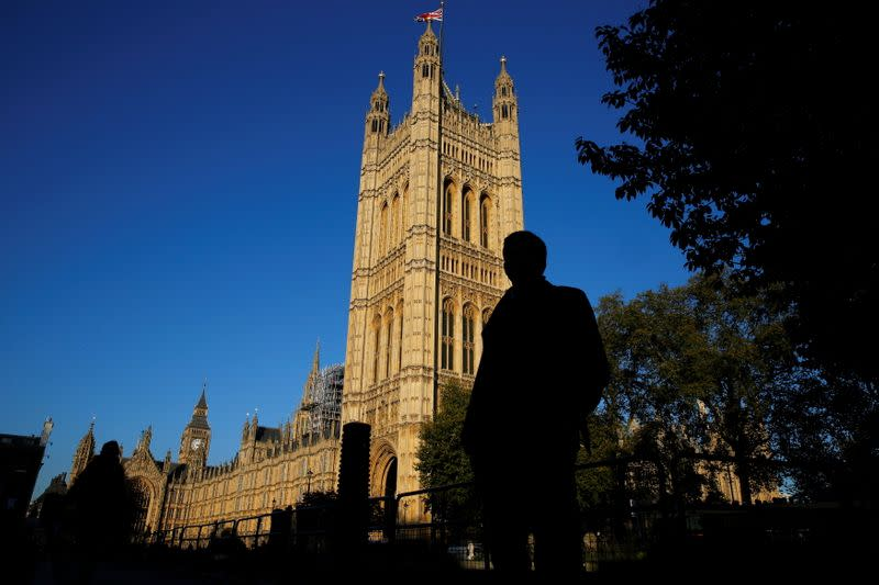 FILE PHOTO: People are silhouetted against the Houses of Parliament in central London