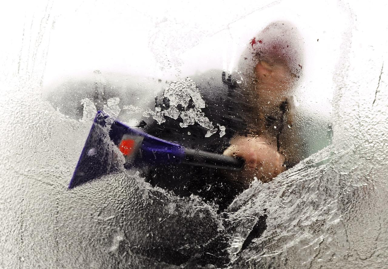 Tyla Crocker uses her lunch break from her job at J.C. Penney's at the Bangor Mall to scrape the ice from her car windows in Bangor, Maine December 22, 2013. A band of severe weather that brought tornadoes and heavy storms to the southeastern United States pushed up the East Coast December 22, bringing record high temperatures to Philadelphia and New York City and ice storms to parts of New England. REUTERS/Kevin Bennett|Bangor Daily News (UNITED STATES - Tags: ENVIRONMENT) NO SALES. NO ARCHIVES. FOR EDITORIAL USE ONLY. NOT FOR SALE FOR MARKETING OR ADVERTISING CAMPAIGNS